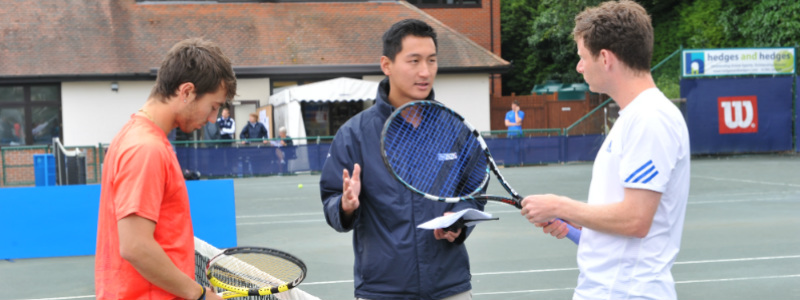 A tennis coach teaching tactics to tennis players