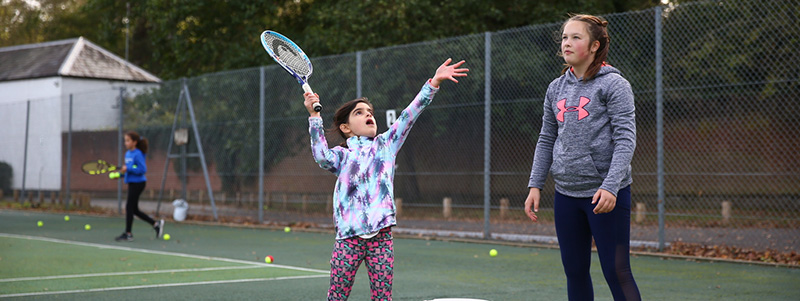 Girl throws a ball up to server during a coaching session