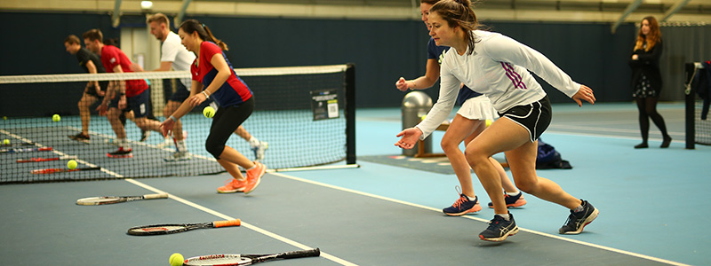 Participants run towards their tennis racket in a cardio tennis session