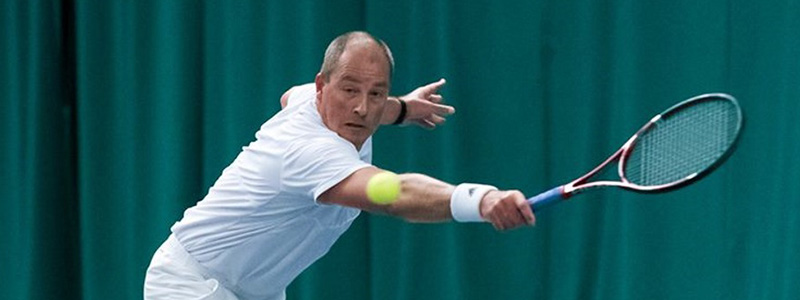 Tennis player reaching for a backhand