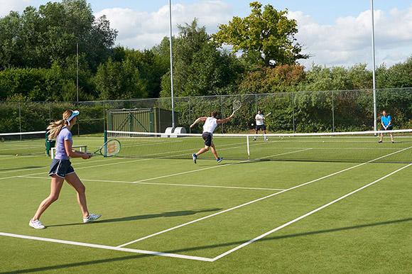 A doubles tennis match being played on a grass court