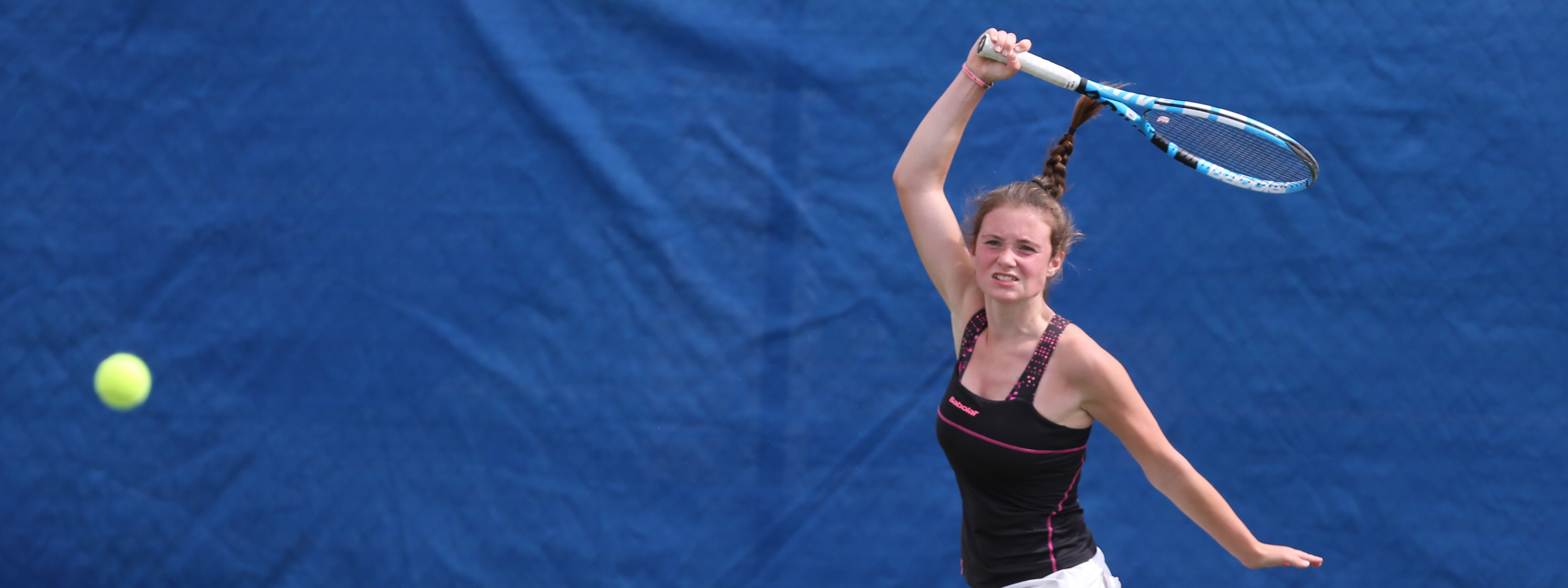 A girl prepares to hit a tennis forehand