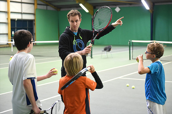 A coach working with three children on court