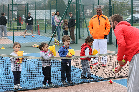 Two tennis volunteers on court coaching a group of children