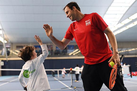 Former British tennis player Greg Rusedski coaching a junior player