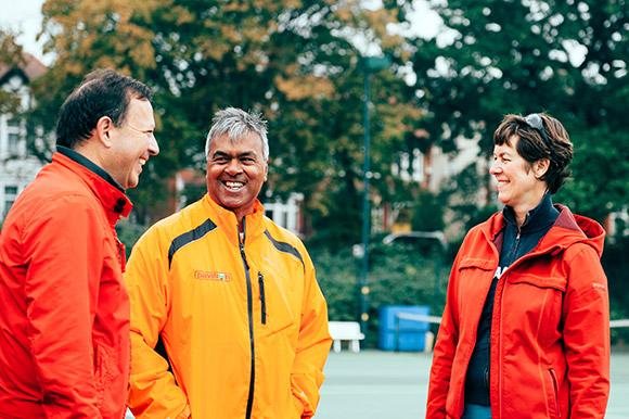 Three tennis volunteers chatting on court