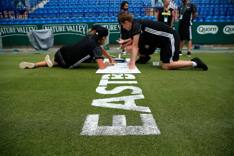 Ground staff apply the finishing touches to the grass courts