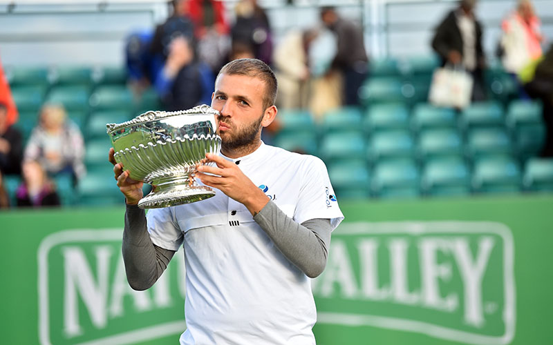 Dan Evans kisses his trophy