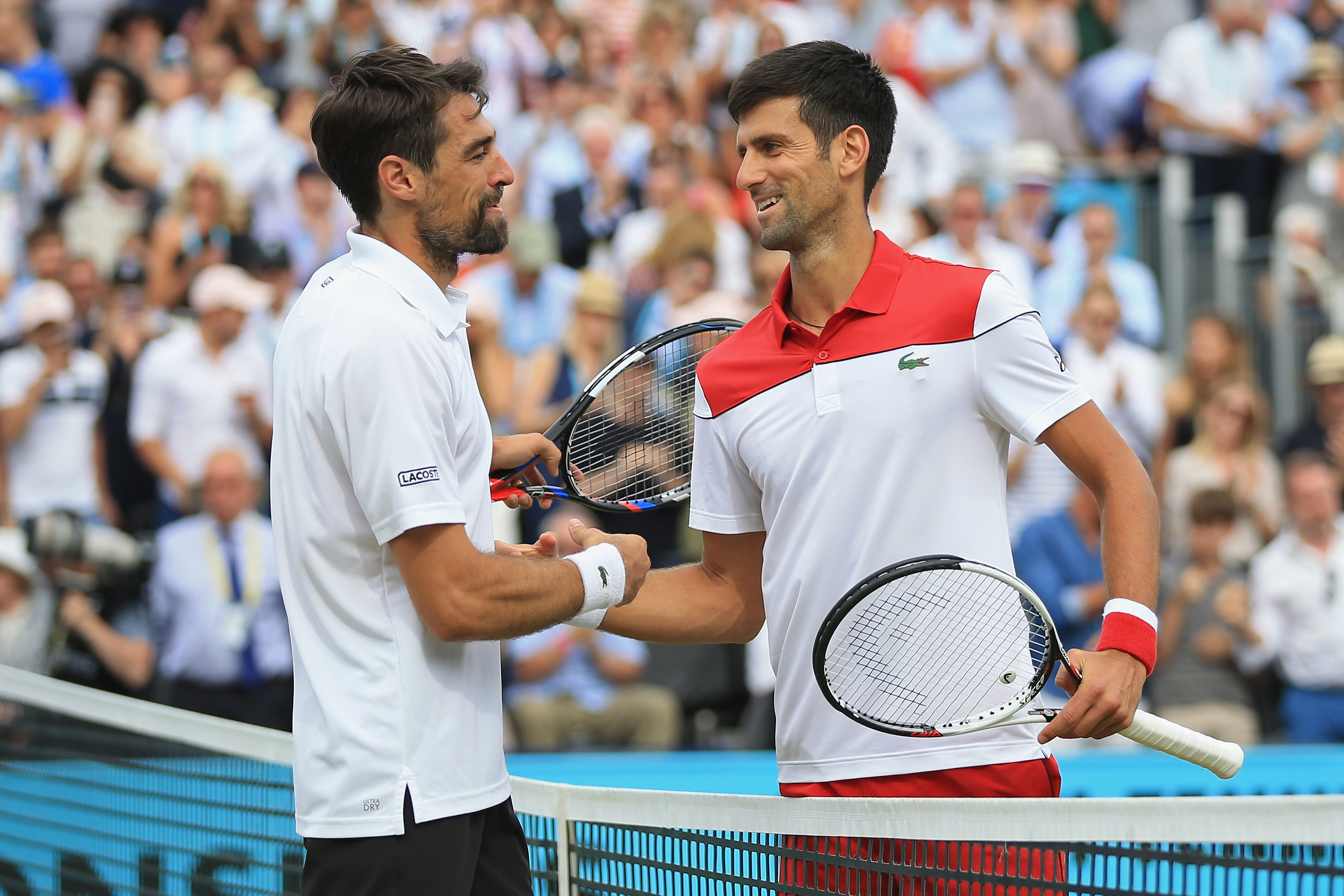 Novak Djokovic smiles and shakes hands with Jeremy Chardy after defeating him to reach the final