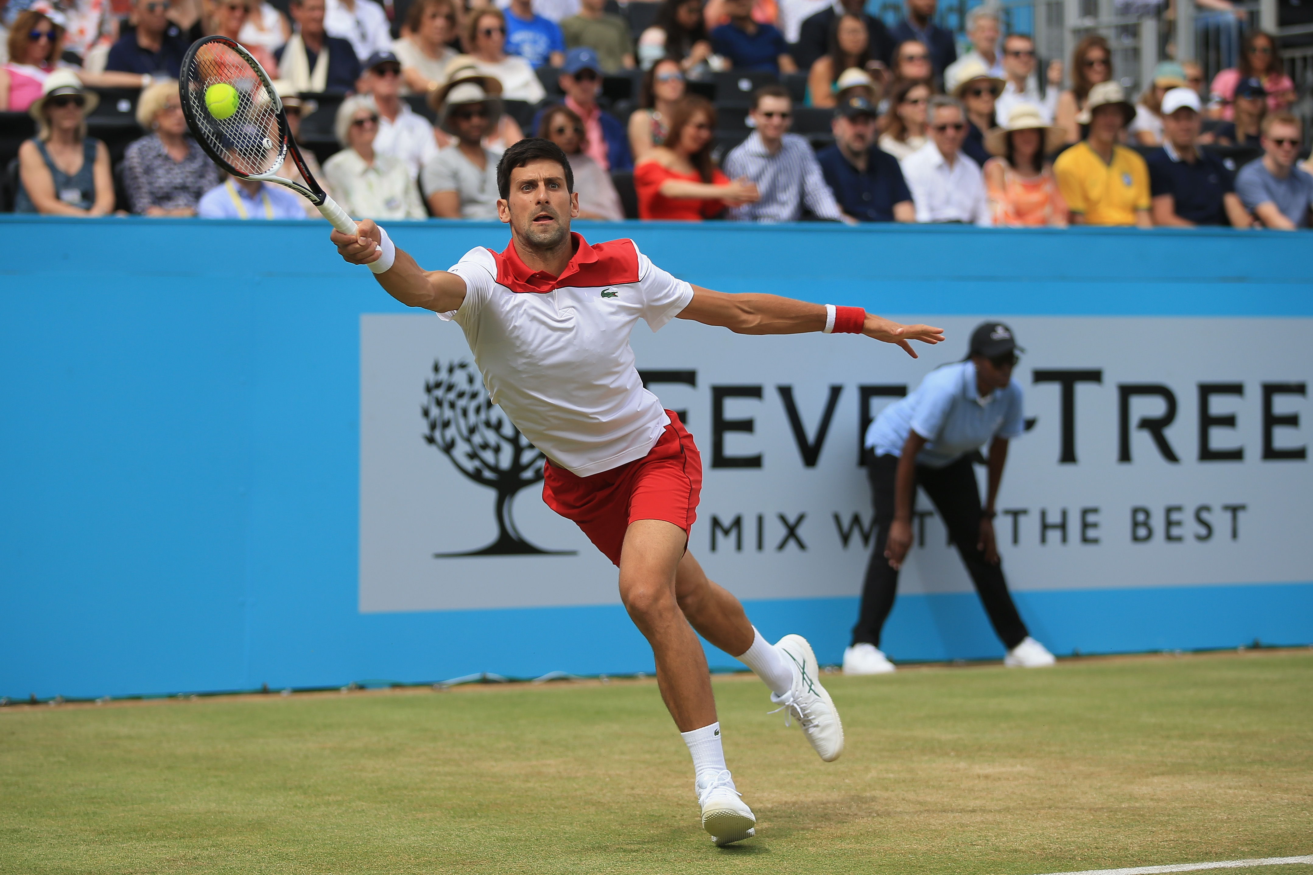 Novak Djokovic leaps for a forehand across the basline during the semi-finals