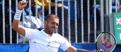 Dan Evans smiles at the Surbiton Trophy as he progresses to the final