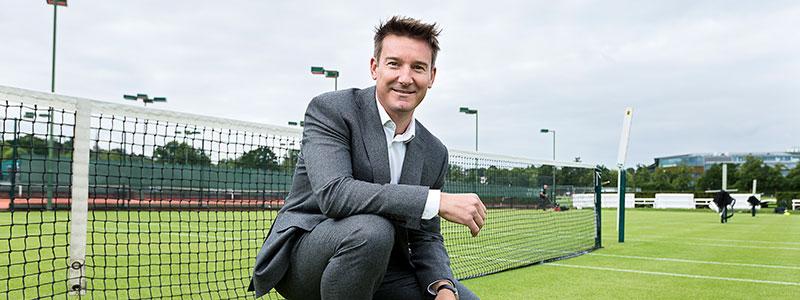 Scott Lloyd poses for photographs on a tennis court