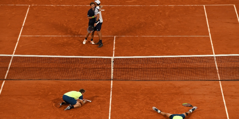 A doubles pair celebrate while another look deflated at Roland Garros