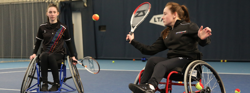 Two wheelchair tennis players in action