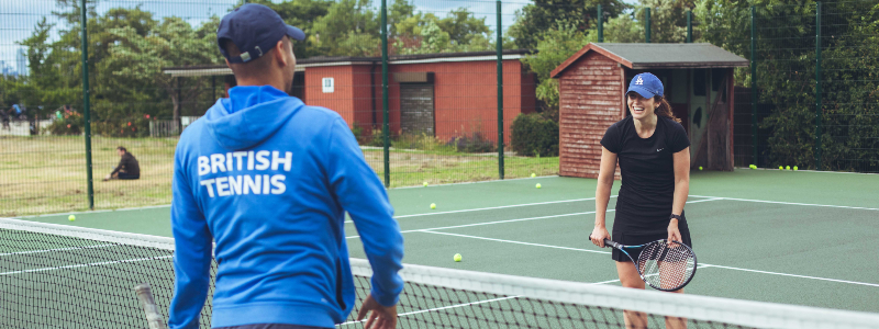 An amateur tennis player receives a lesson from a coach