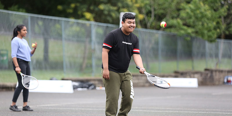 A man enjoying playing tennis in a park