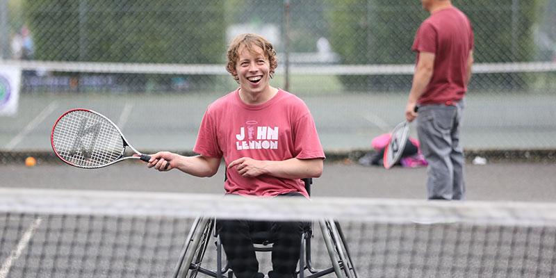 A man enjoys playing wheelchair tennis in a park