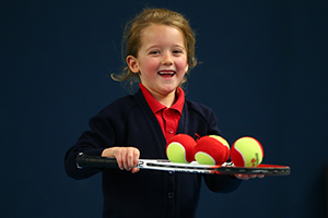 Young child holding racket and tennis balls