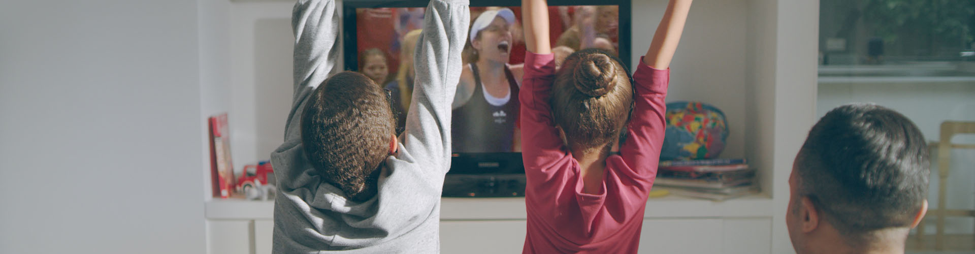 Two children celebrate watching the Fed Cup at home