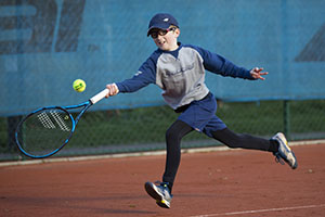 Boy hits a forehand during a LTA Youth competition