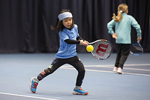 Girl hits a backhand during a LTA Youth competition