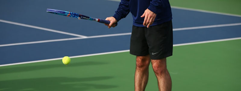 Man bouncing ball with his racket