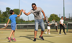 Adult and child high five during a tennis session