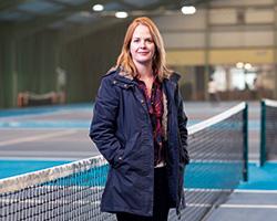 Welfare officer stood at the tennis net