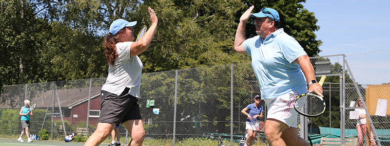 Two adults high five during a tennis session at Sheen common